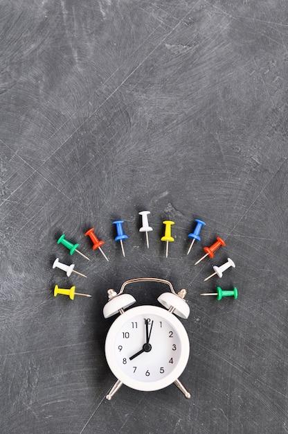 Réveil, crayons de couleur et papeterie sur tableau noir Photo Premium
