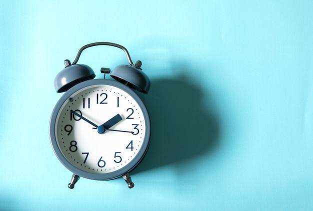 Le réveil sur fond bleu clair, concept de gestion du temps Photo Premium