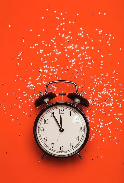 Réveil Sur Fond Rouge Avec Des Paillettes Festives. Concept De Fond Minimal De Nouvel An. Photo Premium