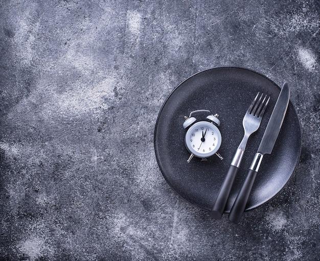 Réveil gris dans une assiette vide. Photo Premium