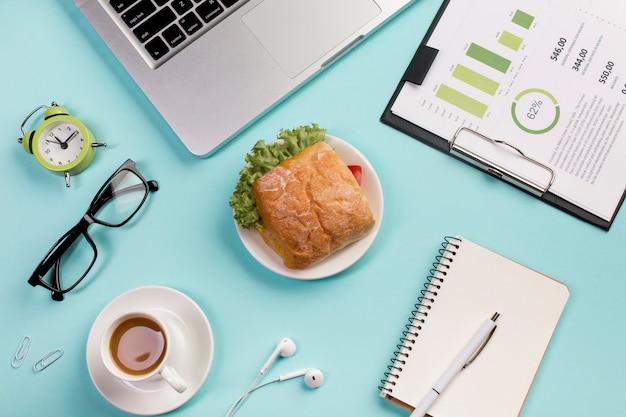 Réveil, Lunettes, Petit-déjeuner, écouteurs, Bloc-notes à Spirale Et Plan Budgétaire Dans Le Presse-papiers Sur Fond Bleu Photo gratuit