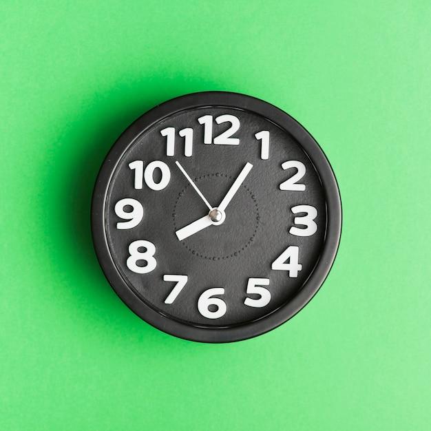 Réveil noir sur fond vert Photo gratuit