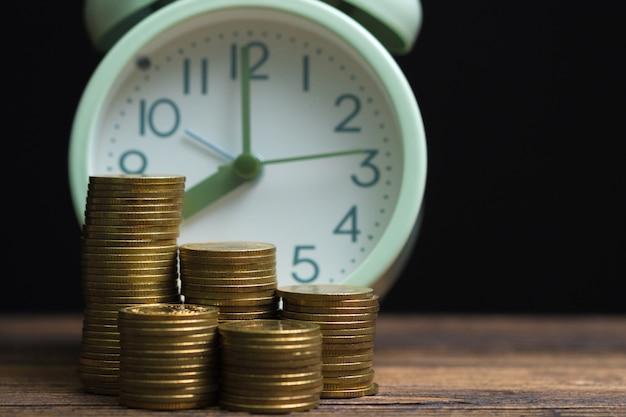 Réveil et pièces de monnaie sur le travail Photo Premium