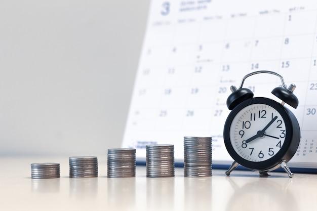 Réveil et pile de pièces d'argent avec fond de calendrier Photo Premium