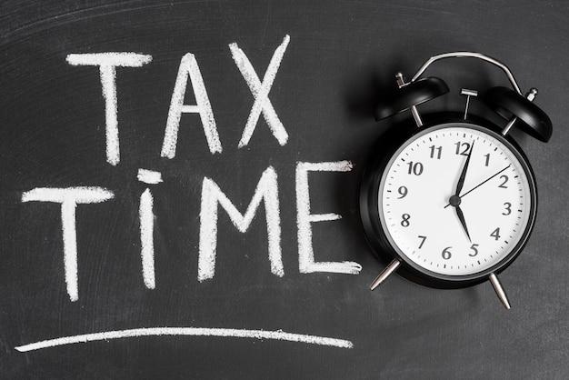 Réveil près du mot temps de taxe écrit sur le panneau noir avec craie Photo gratuit