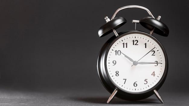 Réveil rétro noir sur fond noir Photo gratuit