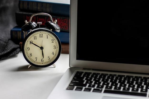 Réveil rétro noir et ordinateur portable avec des livres sur un fond sombre Photo Premium
