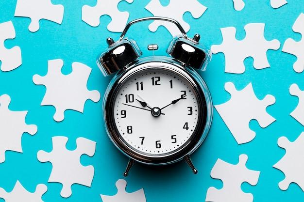 Réveil rétro et pièces de puzzle sur fond bleu Photo gratuit