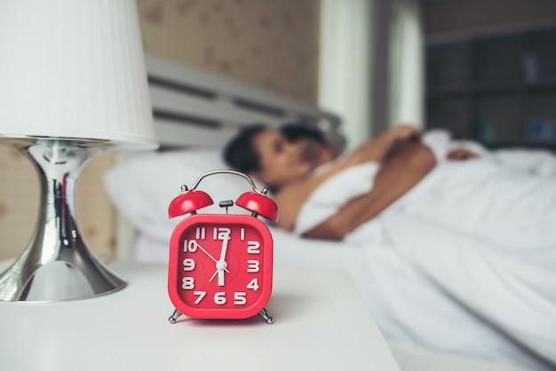 Réveil rouge avec couple dormant confortablement au lit à la maison Photo gratuit