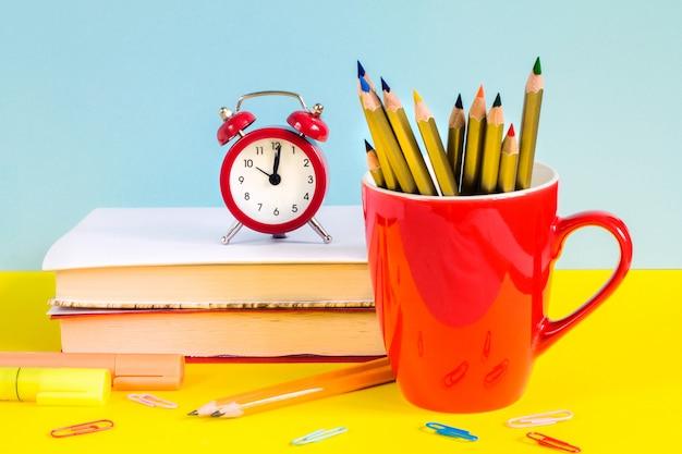 Réveil rouge, crayons de couleur, livres et feuille d'érable sur fond bleu. Photo Premium