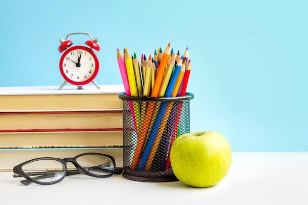 Réveil rouge, pomme, crayons de couleur, livres sur bleu Photo Premium