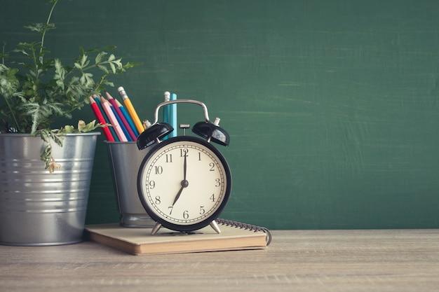 Réveil sur une table en bois sur fond de tableau noir dans la salle de classe Photo Premium