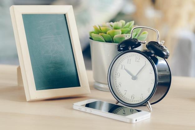 Réveil avec téléphone portable sur une table en bois Photo Premium