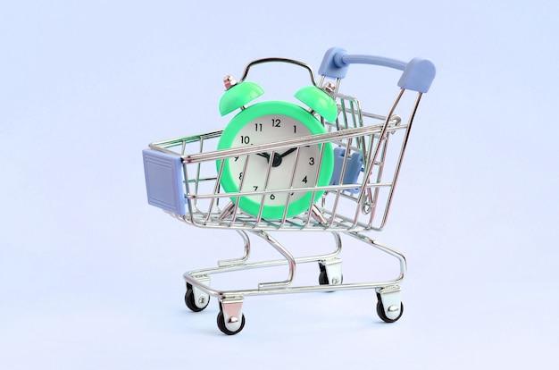 Réveil Vert Dans Le Chariot De Supermarché Sur Bleu Photo Premium