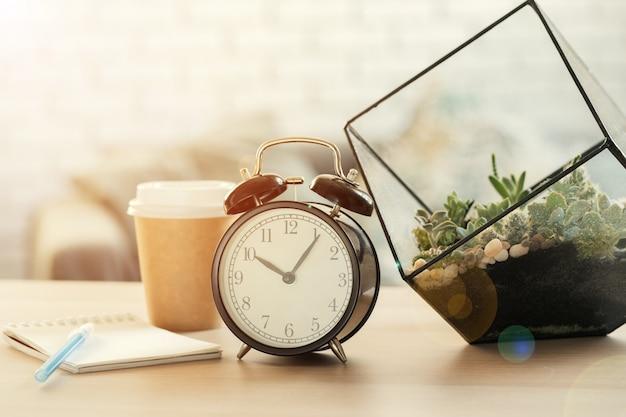 Réveil vintage classique et tasse à café sur fond en bois Photo Premium