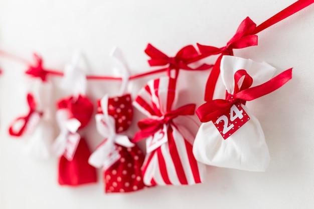 Réveillon de noël. calendrier de l'avent. sacs rouges et blancs avec des bonbons sur un blanc. cadeaux pour les enfants Photo Premium