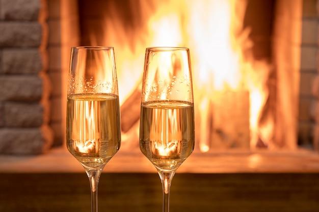 Réveillon de noël. deux verres de vin près de la cheminée, dans une maison de campagne. Photo Premium