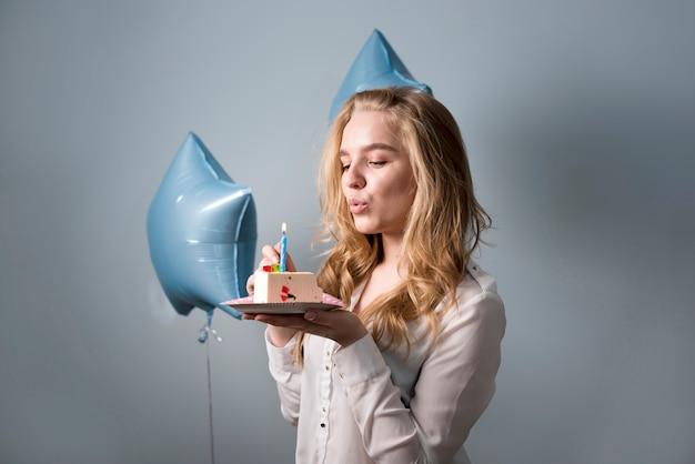Rêveuse jeune femme soufflant bougie sur le gâteau Photo gratuit