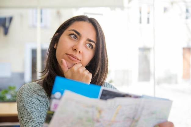 Rêveuse jolie jeune femme à l'aide de la carte en papier au café Photo gratuit