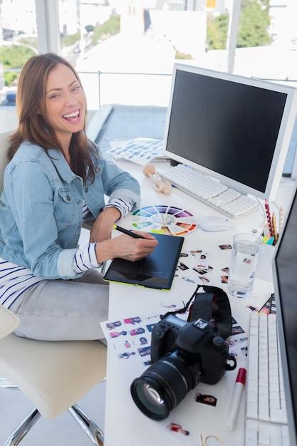Riant éditeur de photos travaillant avec une tablette graphique Photo Premium