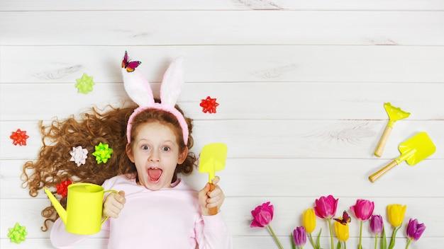 Riant fille dans les oreilles de lapin, allongé sur le plancher en bois. joyeuses pâques, fête des mères, concept de l'enfance. Photo Premium