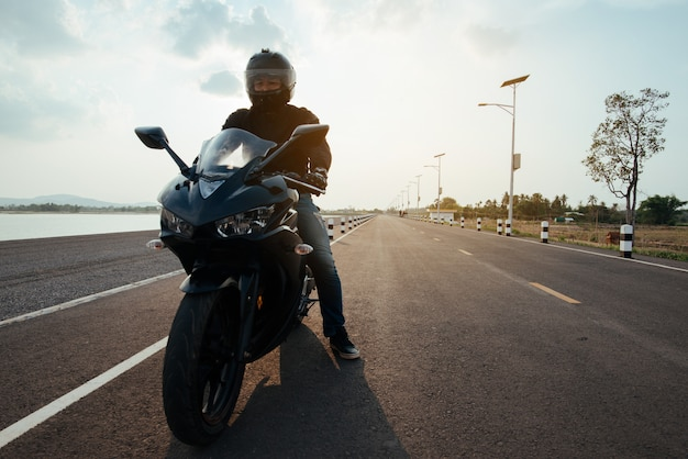 Rider moto sur la route à cheval. s'amuser au volant de la route vide Photo gratuit
