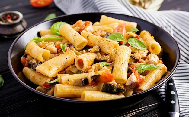 Rigatoni pâtes à la viande de poulet, aubergines à la sauce tomate dans un bol. Photo Premium