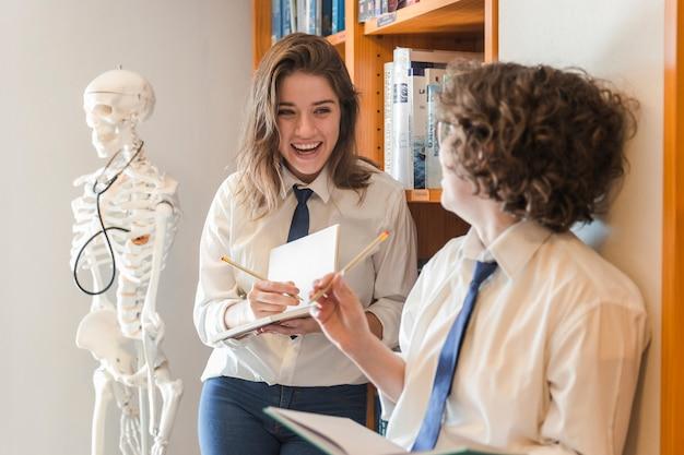 Rire des adolescents prenant des notes dans la bibliothèque Photo gratuit