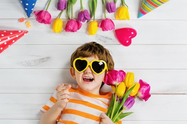 Rire bébé couché sur le plancher en bois avec des lunettes pour forme de coeur sur la fête de carnaval Photo Premium