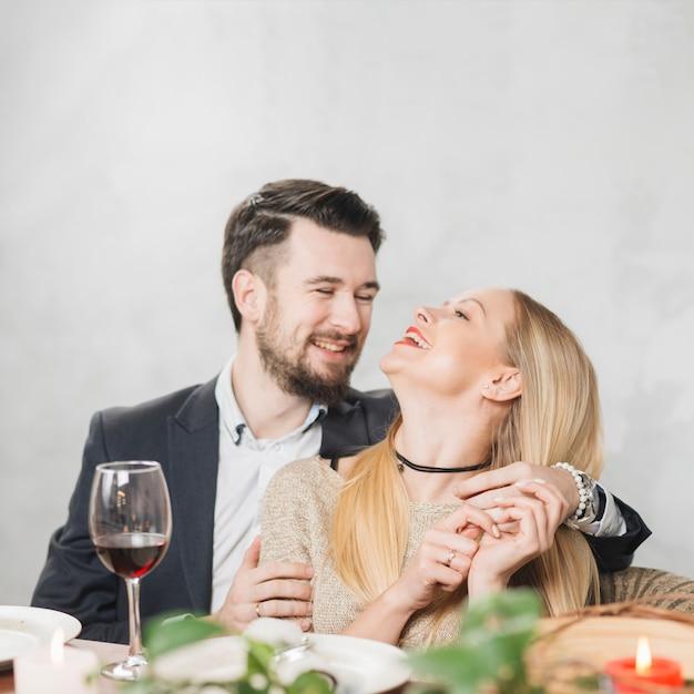 Rire couple amoureux lors d'un dîner romantique Photo gratuit