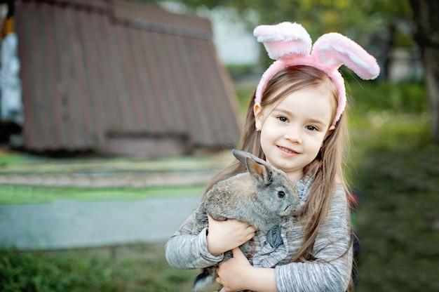Rire enfant à la chasse aux oeufs de pâques avec lapin blanc. Photo Premium