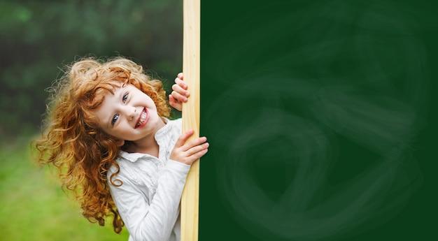 Rire enfant avec tableau noir scolaire montrant des dents blanches en bonne santé. Photo Premium