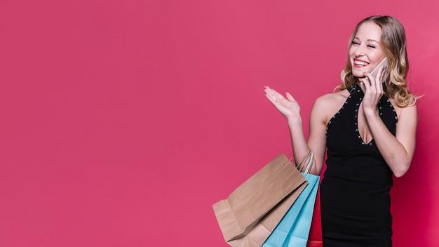 Rire femme blonde avec des sacs parlant au téléphone Photo gratuit