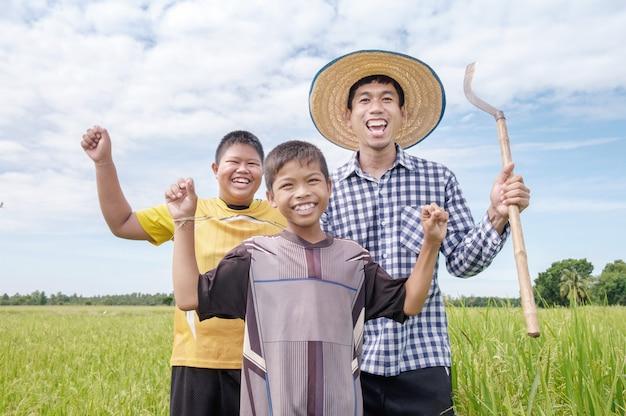 Rire heureux homme agriculteur asiatique et deux enfants sourient et tenant des outils à rizière verte Photo Premium