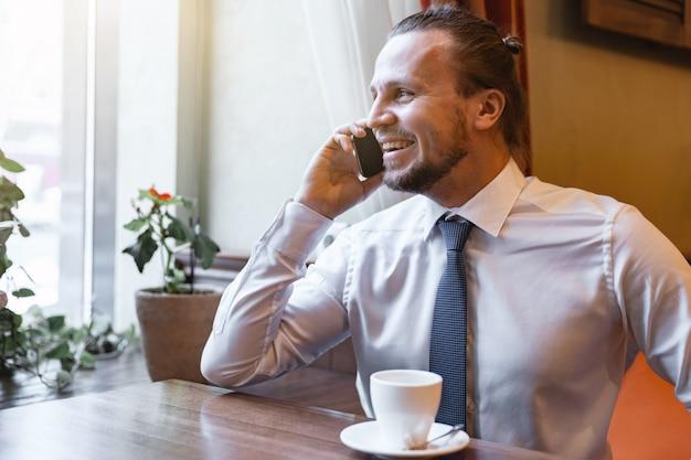 Rire homme appelant sur le téléphone portable assis dans le restaurant intérieur vêtu de chemise blanche Photo Premium