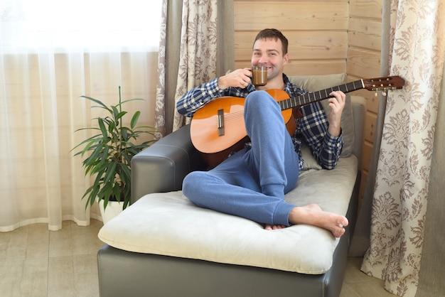Rire Homme Jouant De La Guitare Et Boire Du Café Photo Premium