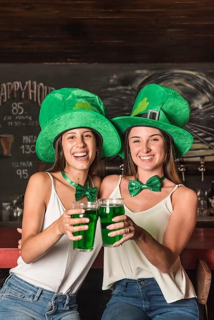 Rire de jeunes femmes en chapeaux saint patricks étreignant et tenant des verres de boisson au bar Photo gratuit