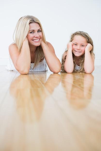 Rire mère et fille se reposant sur le sol Photo Premium