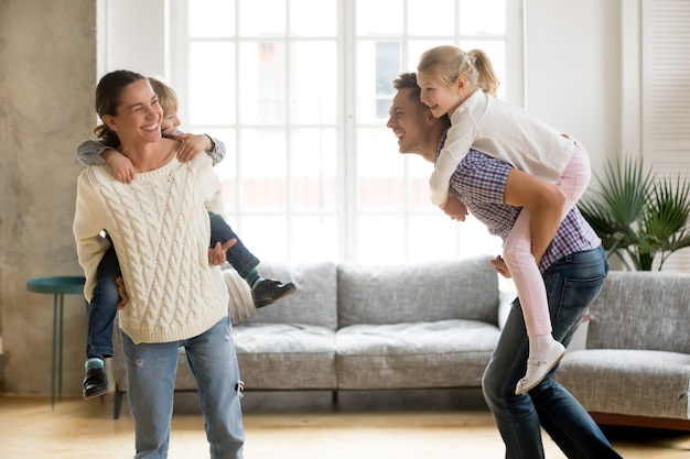 Rire Les Parents Donnant Aux Enfants Piggyback Ride Jouer Ensemble à La Maison Photo gratuit