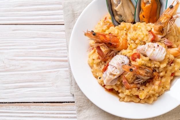 Risotto aux fruits de mer (crevettes, moules, poulpe, palourdes) et tomates Photo Premium