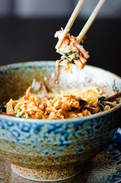 Riz asiatique avec viande de porc, champignons mu-err, chou napa, pousses de bambou marinées, épinards, teriyaki, sauce chili douce, chips d'oignon dans un bol en céramique. Photo Premium
