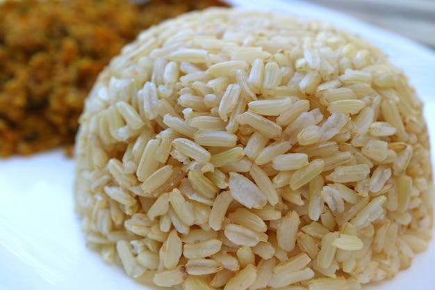 Riz au jasmin brun thaï cuit à la vapeur fermé sur une assiette blanche Photo Premium