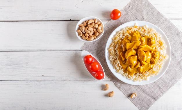 Riz au poulet sauce curry à la noix de cajou sur un fond en bois blanc. Photo Premium