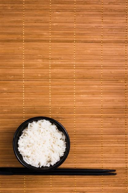 Riz blanc cuit à la vapeur dans un bol en céramique noire avec des baguettes Photo gratuit