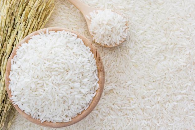 Riz blanc dans un bol et un sac, une cuillère en bois et un plant de riz sur fond de riz blanc Photo Premium