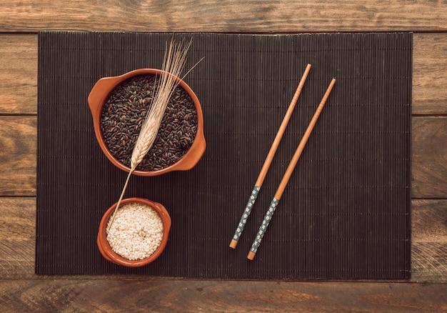 Riz blanc et rouge bio avec tige et baguettes sur plateau en bois Photo gratuit