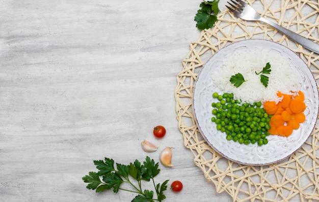 Riz cuit avec des légumes sur une assiette près de la fourchette Photo gratuit