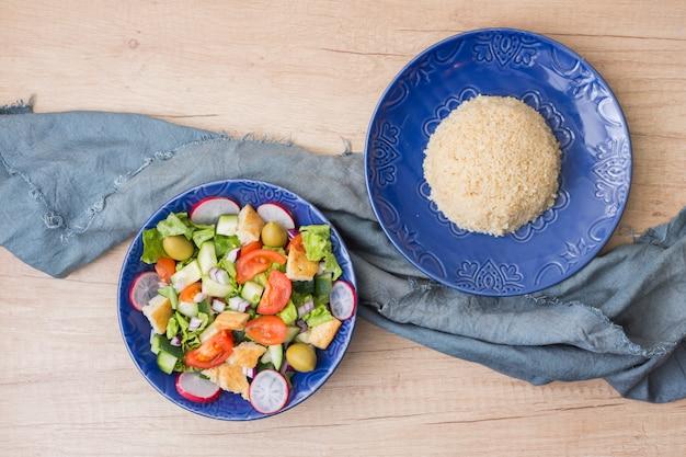 Riz cuit avec salade de légumes sur une table lumineuse Photo gratuit