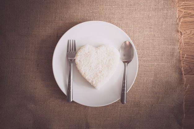 Riz en forme de coeur sur plaque blanche Photo Premium