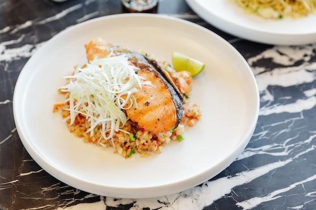 Riz frit à l'ail avec du saumon grillé servi avec une sauce aux haricots pimentés sur une table en marbre noir. Photo Premium